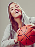 Sporty teen girl in hood holding basketball. Royalty Free Stock Image