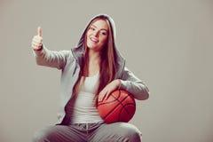 Sporty teen girl in hood holding basketball. Stock Photo