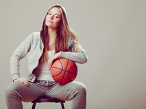 Sporty teen girl in hood holding basketball. Royalty Free Stock Photos