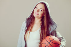 Sporty teen girl in hood holding basketball. Stock Photos