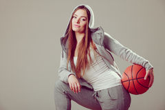 Sporty teen girl in hood holding basketball. Stock Photography