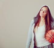 Sporty teen girl in hood holding basketball. Stock Images