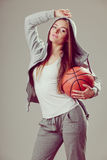 Sporty teen girl in hood holding basketball. Stock Photos