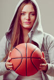 Sporty teen girl in hood holding basketball. Royalty Free Stock Photography