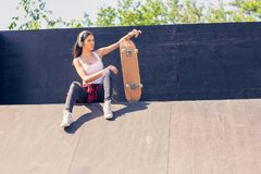 Sporty teen girl with skateboard listening music. Outdoors, urban lifestyle stock photography