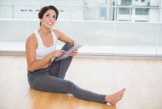 Sporty thoughtful brunette using tablet sitting on the floor Royalty Free Stock Photos
