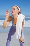 Sporty tired blonde drinking water on the beach Royalty Free Stock Photo