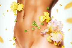 Sporty torso of woman in yellow flowers. With flying petals Stock Photo