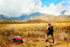 Sporty tourist guy with backpack looking at the mountains. Indonesia. Lombok Island.  Stock Photo