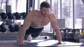 Sporty trenuje, mięśniowy sportowiec z pięknym sportowym ciałem robią pushups podczas władza treningu przy sprawność fizyczna klu zbiory