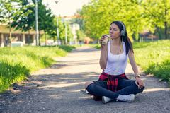 Sporty urban girl sitting on skateboard and listening music. Outdoors, urban lifestyle stock images