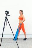 Sporty videoblogger женщины разрабатывая с диапазонами латекса Стоковое Изображение