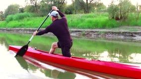 Sporty wiosłuje na kajaku Mężczyzna pławiki zestrzelają rzekę wzdłuż drewna zbiory