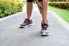Sporty woman ankle sprain while jogging or running at park. Sporty woman ankle sprain while jogging or running at park Royalty Free Stock Photography