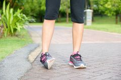 Sporty woman ankle sprain while jogging or running at park. Sporty woman ankle sprain while jogging or running at park Royalty Free Stock Photos