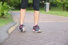 Sporty woman ankle sprain while jogging or running at park.  Royalty Free Stock Photos
