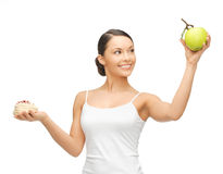 Sporty woman with apple and cake Stock Image