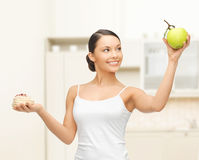 Sporty woman with apple and cake in kitchen Royalty Free Stock Image