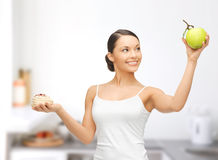Sporty woman with apple and cake in kitchen Stock Image