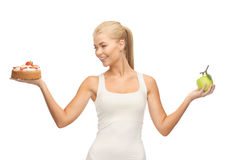 Sporty woman with apple and cake Royalty Free Stock Images