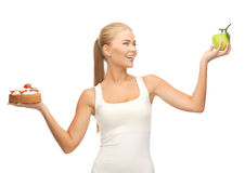 Sporty woman with apple and cake Royalty Free Stock Photo