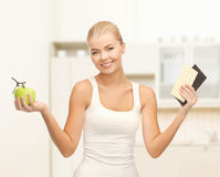 Sporty woman with apple and chocolate bars Royalty Free Stock Photography