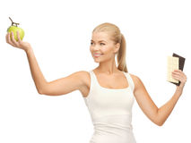Sporty woman with apple and chocolate bars Stock Image