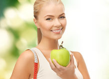 Sporty woman with apple and measuring tape Stock Images