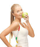 Sporty woman with apple and measuring tape Royalty Free Stock Image