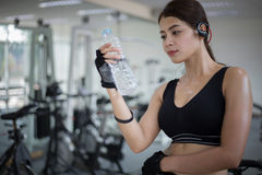 Sporty woman asia drinking water after exercises in the gym. Fit. Ness - concept of healthy Royalty Free Stock Photo