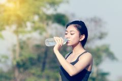 Sporty woman asia holding and drinking water outdoor on sunny da stock image