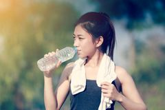 Sporty woman asia holding and drinking water outdoor on sunny da royalty free stock photography