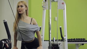 A sporty woman athlete building muscles on his. Back in the gym. the load goes to the latissimus dorsi, blades, rear delts shoulder. She stands in the middle of stock video footage