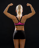 Sporty woman from the back flexing her biceps Stock Photos