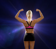 Sporty woman from the back flexing her biceps Royalty Free Stock Photography