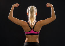 Sporty woman from the back flexing her biceps Stock Photo