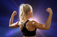 Sporty woman from the back flexing her biceps Stock Image