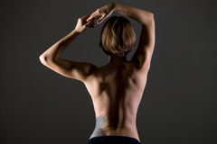 Sporty woman back. Young slim beautiful woman, with perfect body working out, posing, showing back muscles, body sculpture concept, studio image on grey royalty free stock photos