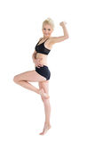 Sporty woman balancing on one leg while stretching out hand Stock Photo
