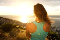 Sporty woman from behind watching the sunset Royalty Free Stock Images