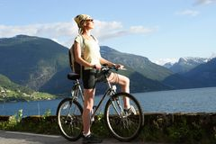 Sporty woman on a bicycle trip in the mountains 2. Healthy woman on her bike trip in the mountains over the lake stock image