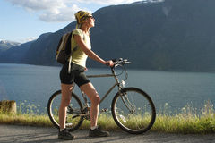 Sporty woman with bike in the mountains. Healthy woman with her bike looking at the mountains over the lake stock photos