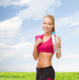 Sporty woman with bottle of water and towel Stock Images