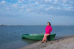 Sporty woman, in a bright jacket, sits on the boat Stock Photography