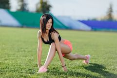 Sporty woman brunette runner in sport wear doing workout sessions on the field in a sports suit in the summer on a hot sunny day. stock photos