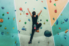 Sporty woman climbing up on practice rock wall indoor. Young sporty woman climbing up on practice rock wall in gym, rear view Royalty Free Stock Images