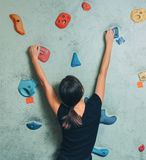 Sporty woman climbing up on rock wall indoor Stock Photos