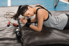 Sporty woman with closed eyes exercising on mat in sports hall Royalty Free Stock Photography