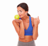 Sporty woman with closed eyes smelling apple Royalty Free Stock Photo