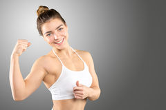 Sporty woman demonstrating biceps Royalty Free Stock Images